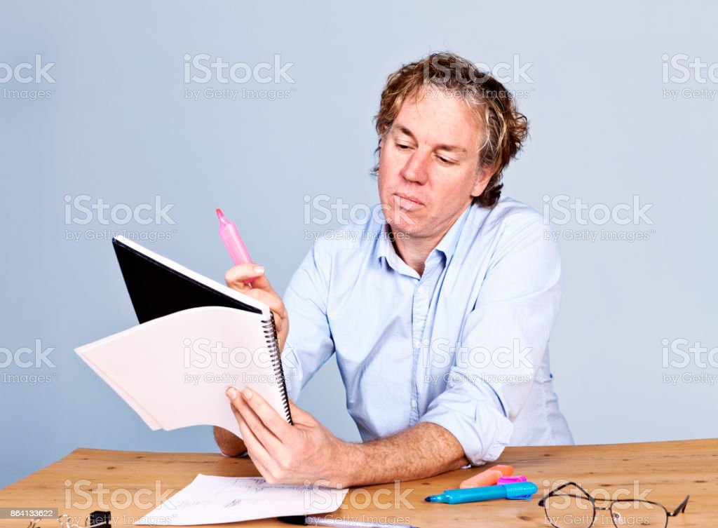 Serious man at desk with notebook, pens, and spectacles royalty-free stock photo