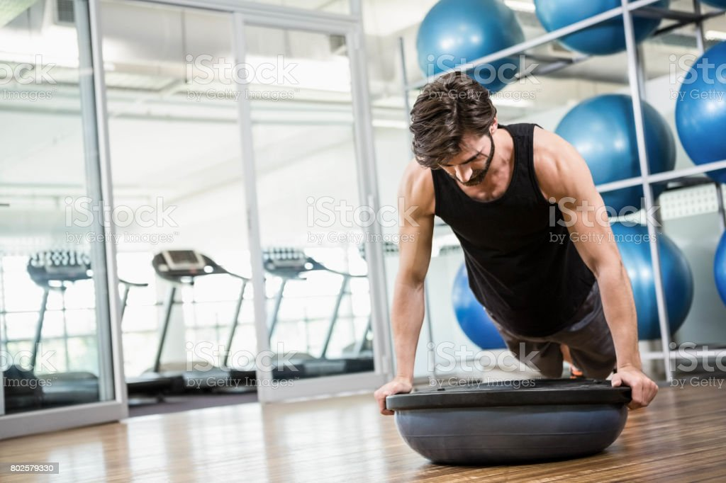Serious man doing exercise with bosu ball stock photo