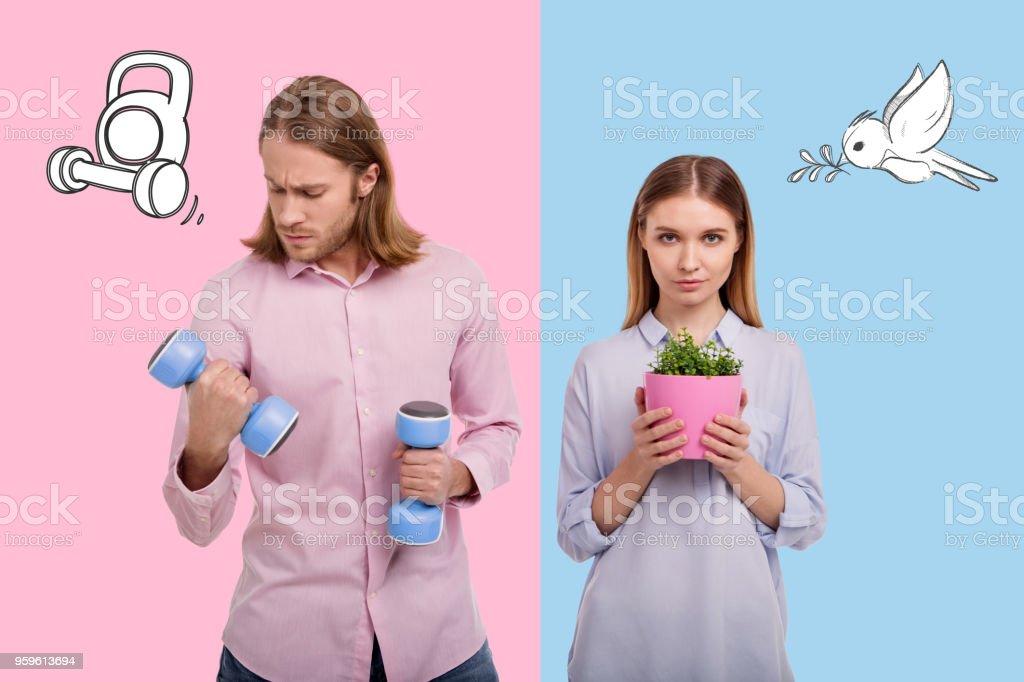 Hombre serio con pesas de mano y su novia tranquila cerca - Foto de stock de Adolescencia libre de derechos