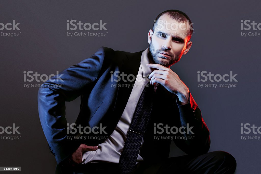 serious man in a business suit, dark background, backlight blue stock photo