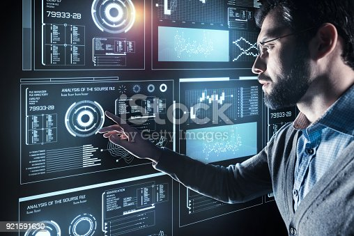 istock Serious man in glasses touching the screen and feeling worried 921591630