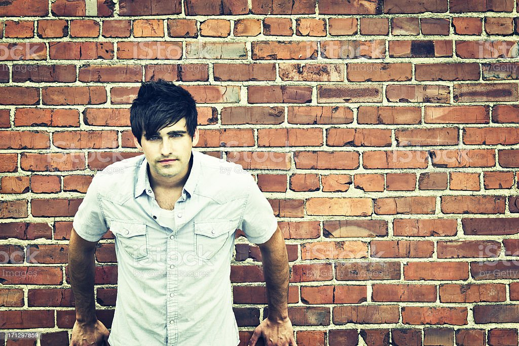 Serious Man Leaning Against Brick Wall stock photo