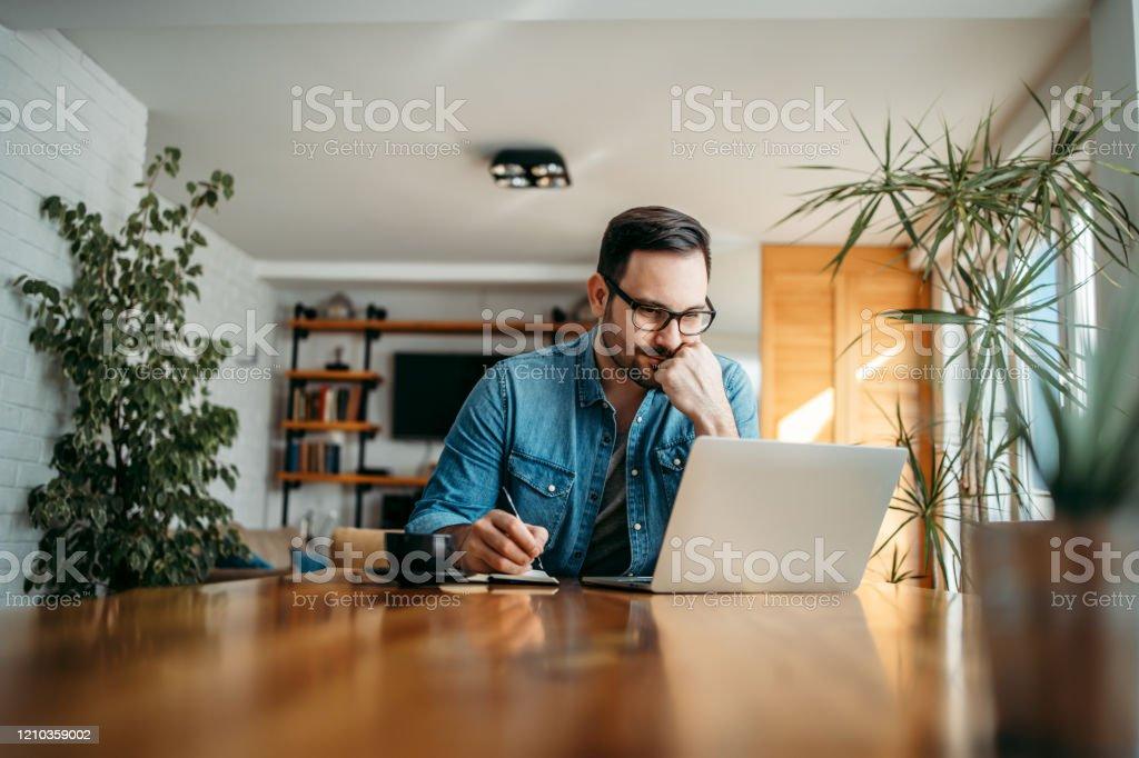 Hombre serio mirando el ordenador portátil y tomando notas en cuaderno, retrato. - Foto de stock de Adulto libre de derechos