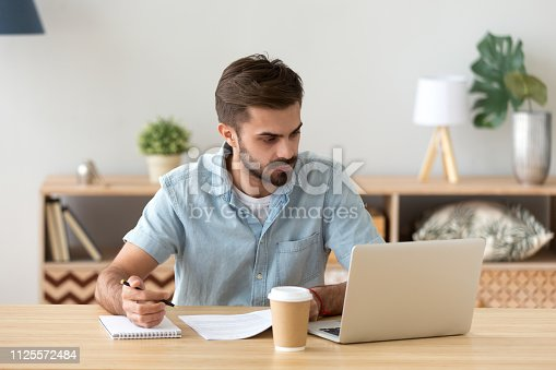 istock Serious man looking at laptop making notes working with documents 1125572484