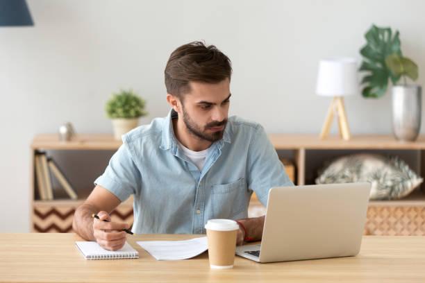 ernster mann blick auf laptop notizen arbeiten mit dokumenten - nachrichten video stock-fotos und bilder