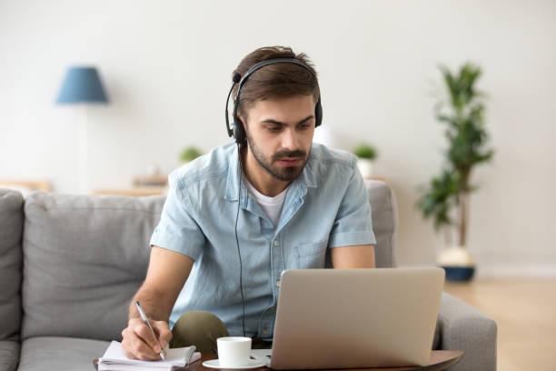 ernster mann blick auf laptop tragen kopfhörer, die fremde sprache zu lernen - nachrichten video stock-fotos und bilder