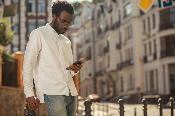 Serious man looking at the smartphone in the street stock photo