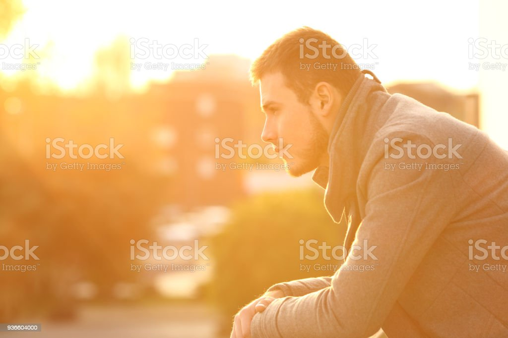 Serious man looking away at sunset in winter stock photo