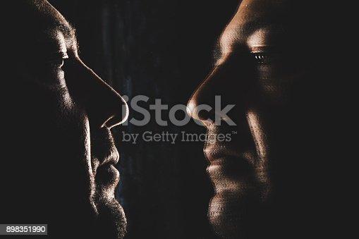 1134770826 istock photo Serious man looking his face through mirror 898351990