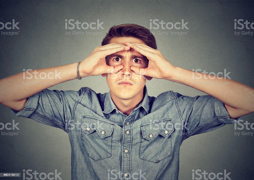 Serious man looking through hands shaped as binoculars royalty-free stock photo