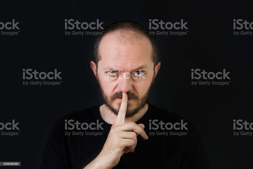 Serious man making silence gesture, pst stock photo