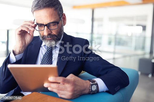 Serious man managing director of prosperous company is holding touch pad