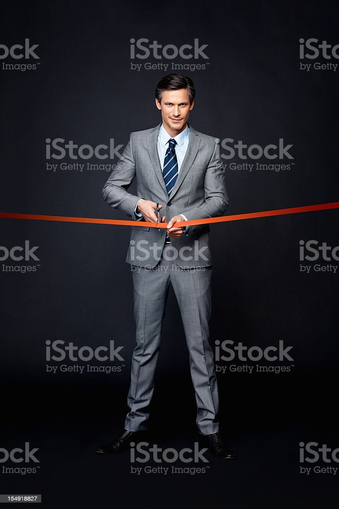 Serious man performing ribbon cutting ceremony royalty-free stock photo