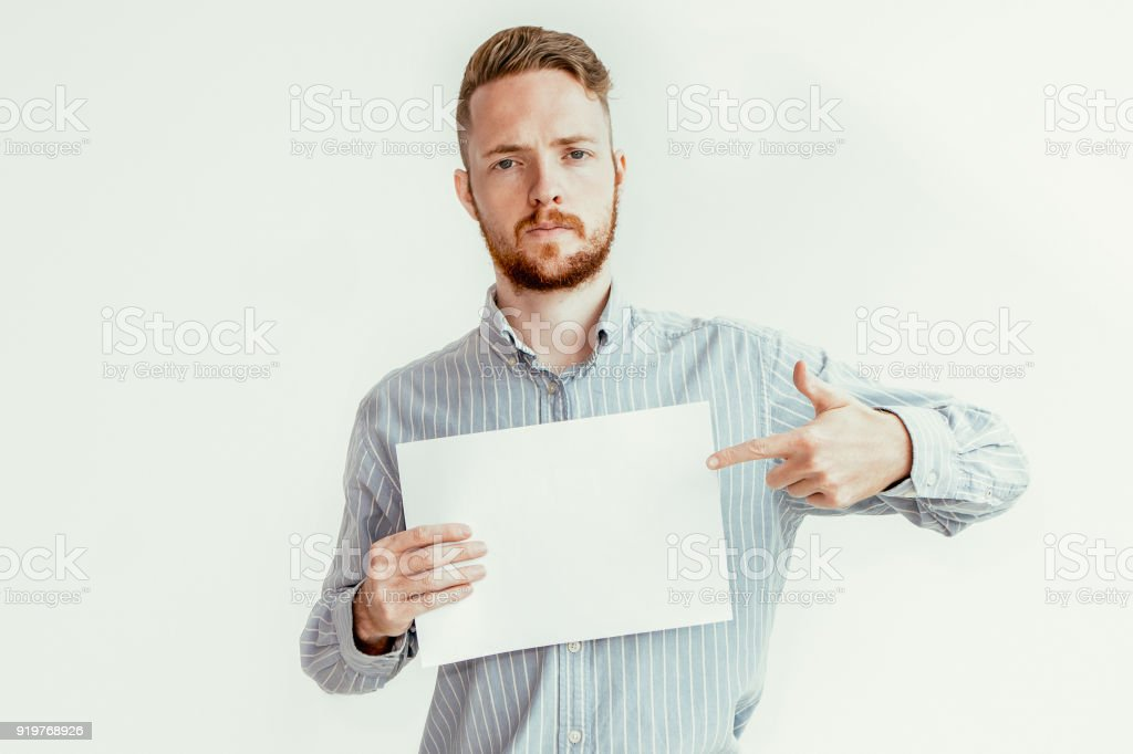 Serious Man Pointing at Blank Sheet of Paper stock photo