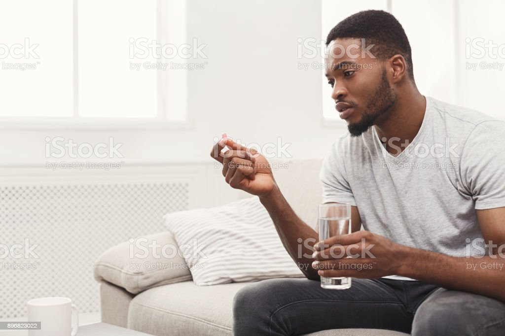 Serious man ready to take a pill sitting on couch stock photo