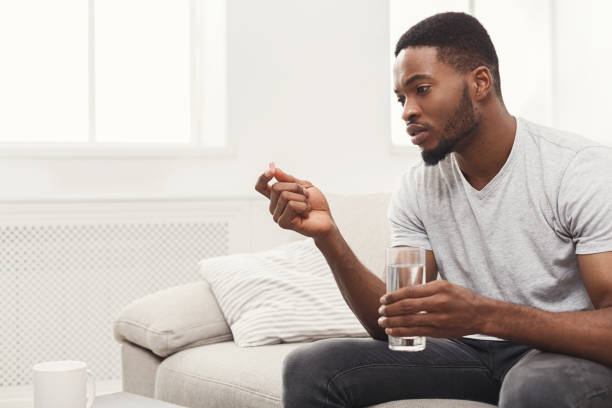 Serious man ready to take a pill sitting on couch Serious african-american man ready to take a pill sitting on a couch at home, copy space woman taking pills stock pictures, royalty-free photos & images