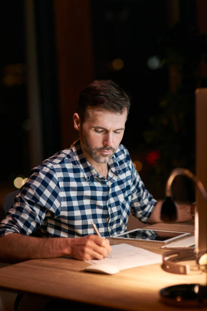 Serious man signing documents at night stock photo