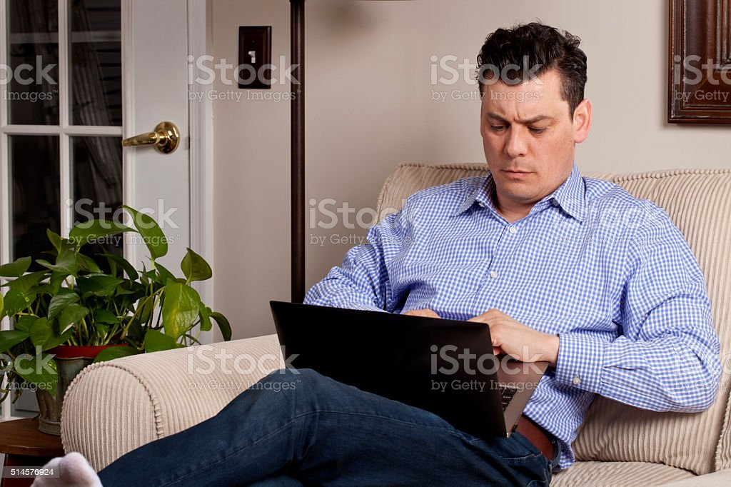 Serious man sitting on couch feet up with laptop stock photo