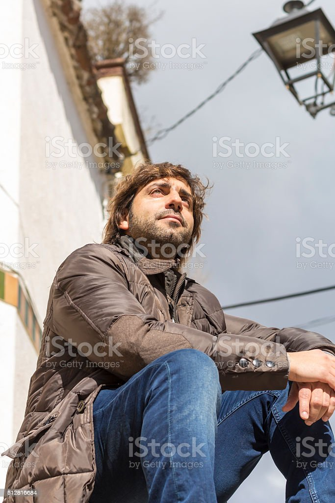 Serious man sitting on steps stock photo