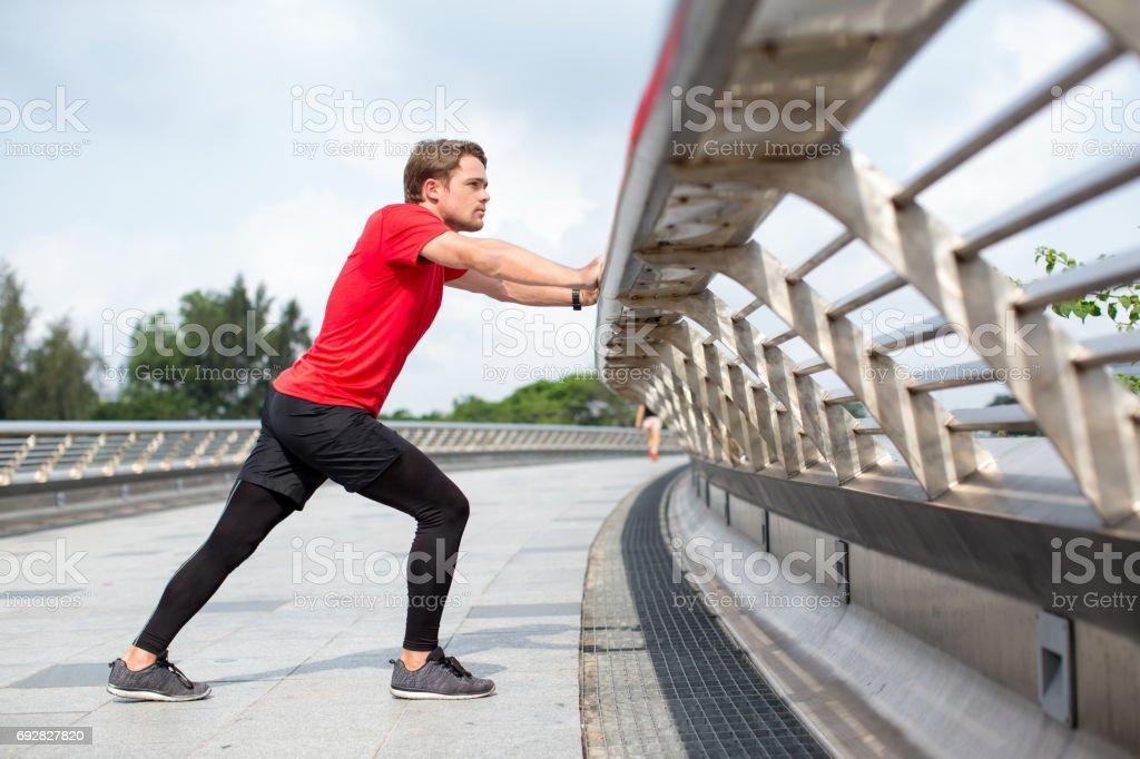 Serious Man dehnen Kalb und stützte sich auf Geländer – Foto