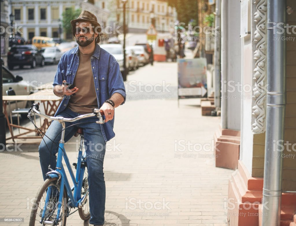 Serious man using gadget while cycling - Royalty-free Adult Stock Photo