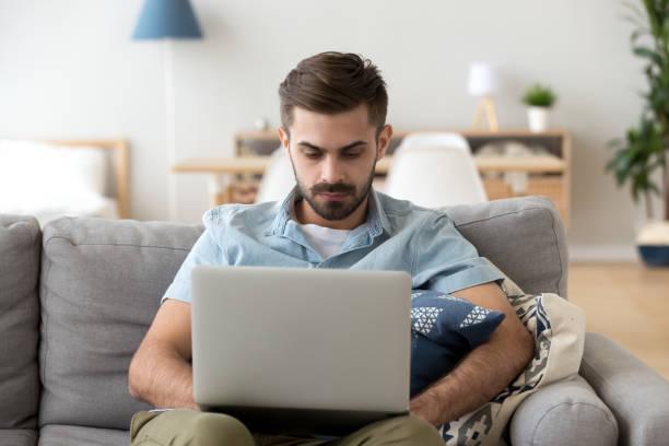 ernster mann mit laptop sitzen auf der couch zu hause arbeiten - nachrichten video stock-fotos und bilder