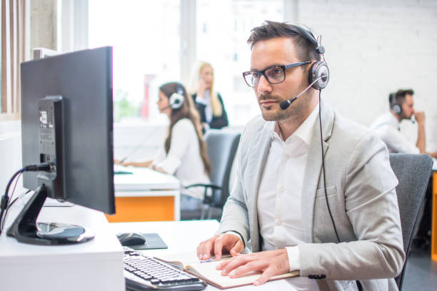 Serious man wearing formal clothes and headset looking at computer screen in bright office stock photo