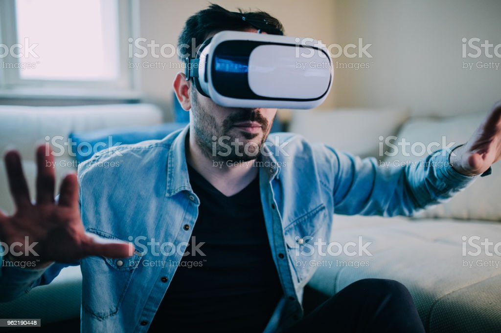 Serious man wearing virtual reality glasses stock photo