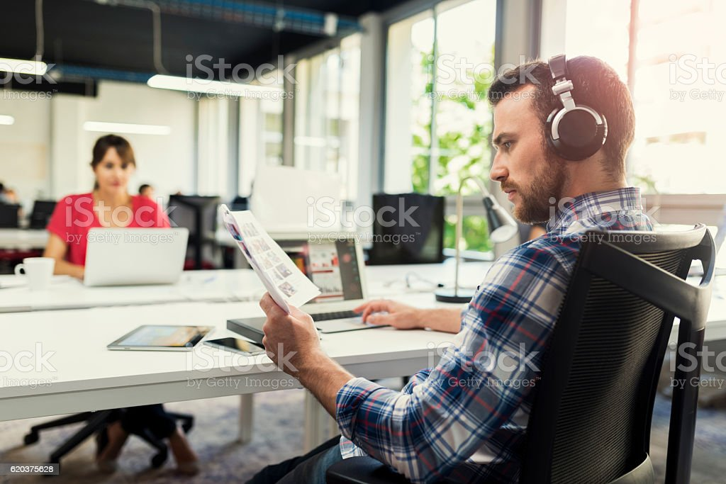 Serious man working on laptop while listening to music zbiór zdjęć royalty-free
