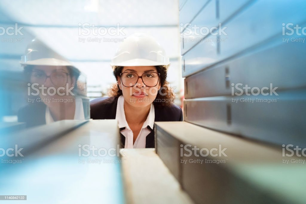 Serious manager inspecting equipment on shelf Serious manager inspecting industrial equipment on shelf. Inspector is on visit in manufacturing industry. She is wearing eyeglasses. 30-34 Years Stock Photo