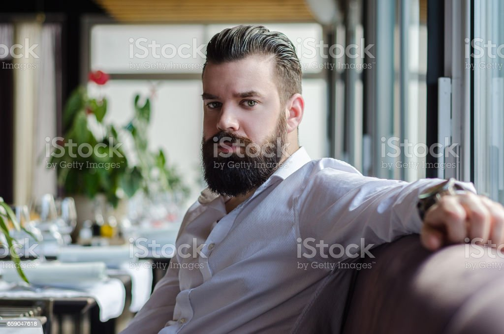 homem viril sério sentado em um restaurante foto royalty-free