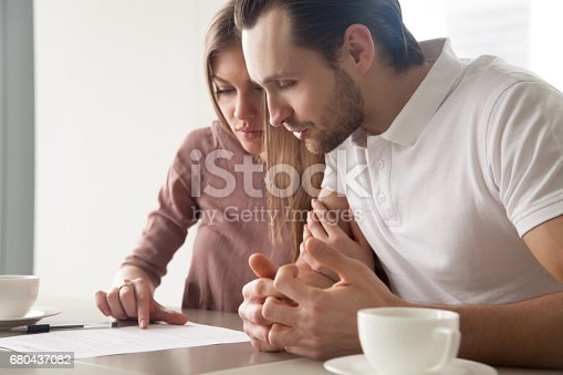 istock Serious married couple with papers, considering loan offer, calculating bills 680437082