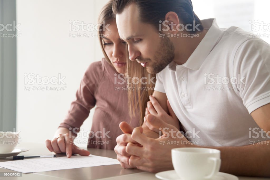 Serious married couple with papers, considering loan offer, calculating bills stock photo