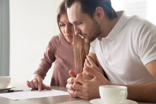 Schweren Ehepaar mit Papieren, Kreditangebot, Berechnung der Rechnungen unter Berücksichtigung – Foto