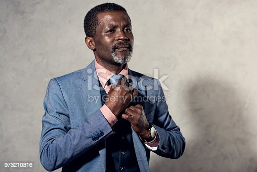973213156 istock photo serious mature african american businessman in blue jacket and tie 973210316