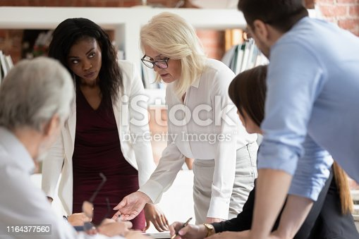 istock Serious mature business woman supervisor teaching workers at group meeting 1164377560