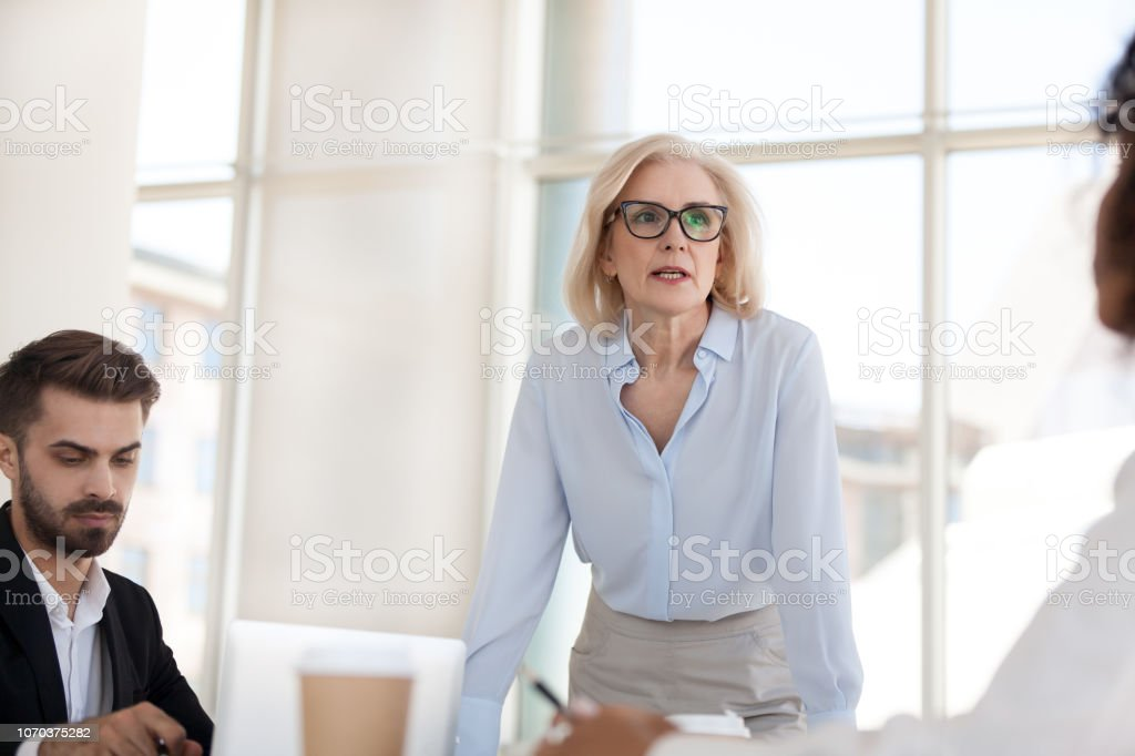Serious mature businesswoman talk having discussion during briefing stock photo