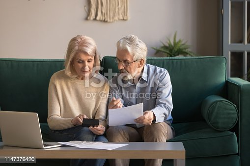 istock Serious mature couple calculating bills, checking domestic finances 1147376420