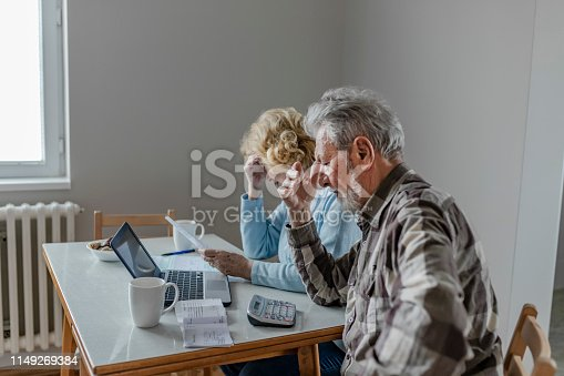 Serious Worried Senior Couple Calculating Bills to Pay or Checking Domestic Finances Stressed of Debt, Retired Elderly Old Family Reading Documents Concerned About Loan Bankruptcy Money Problems. Mature Couple Doing Some Paperwork and Calculations at Home