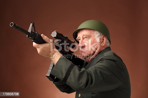 serious mature US soldier aims assault rifle  on plain background - shallow focus on eye