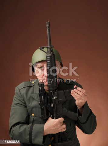 serious mature US veteran soldier with assault rifle  on plain background