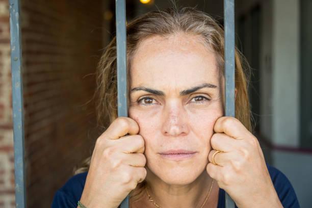 serious mature woman behind bars stock photo