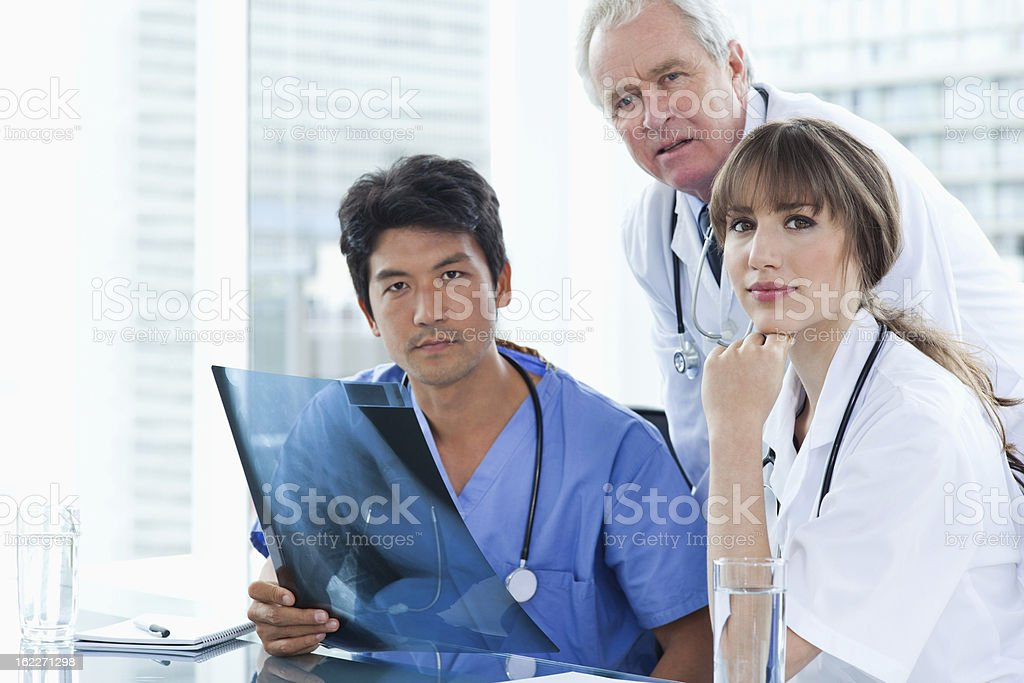Serious medical team working on an x-ray of patient royalty-free stock photo