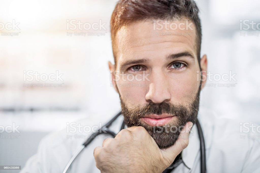 Serious mid adult doctor contemplating and looking at camera. stock photo