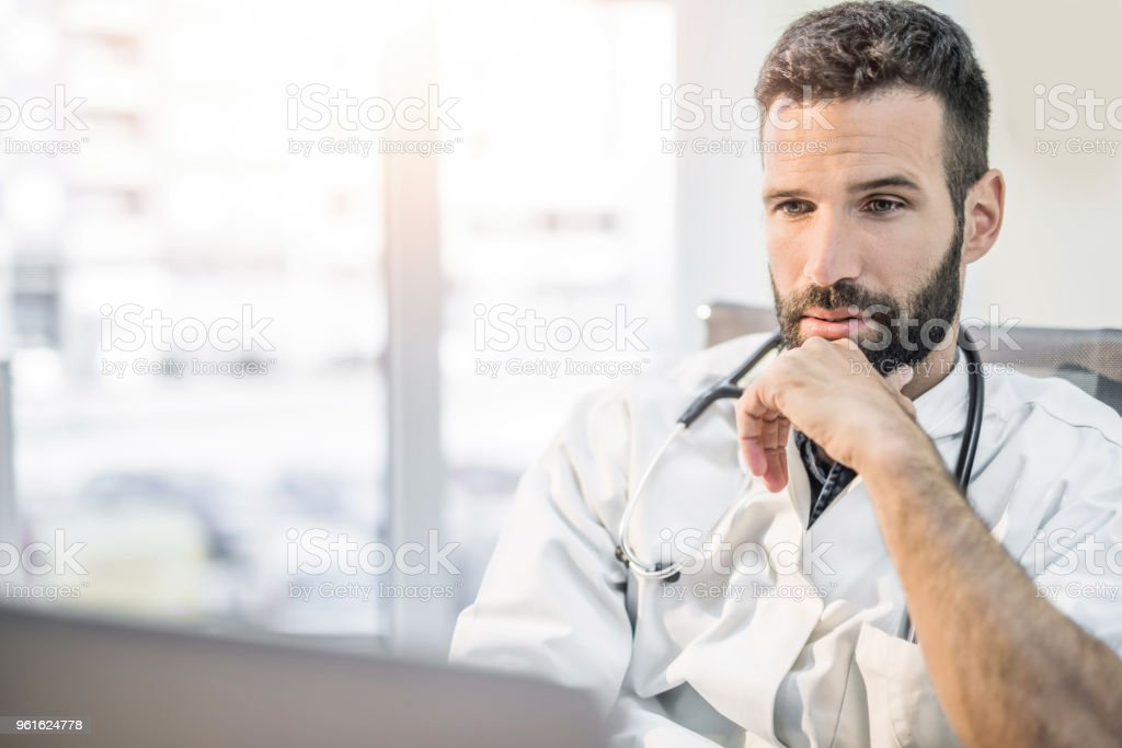 Serious mid adult doctor contemplating and working on laptop. stock photo