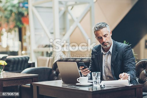 Middle age businessman working in the lobby of a modern business building, with copy space.