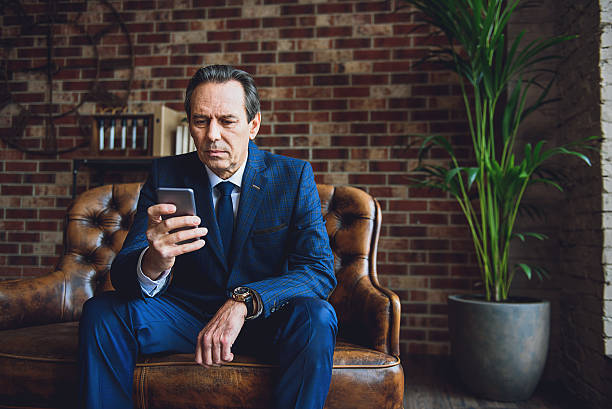 Serious middle aged businessman in room stock photo