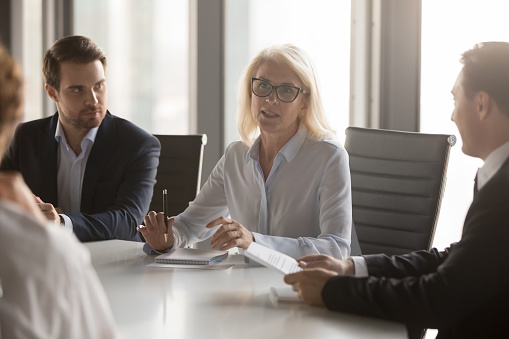 istock Serious middle aged businesswoman talks at group board executive meeting 1128967595