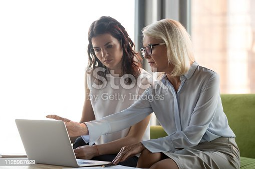 istock Serious middle aged executive manager explaining colleague online work 1128967629