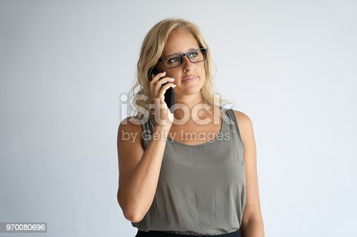 Serious mother at work calling on children. Focused Caucasian woman in glasses talking on mobile phone. Mother at work and communication concept